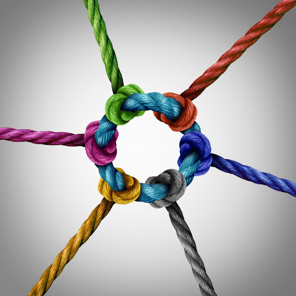 Central network connection business concept as a group of diverse ropes connected to a circle central rope as a network metaphor for connectivity and linking to a centralized support structure.
